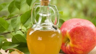 A jar of apple cider vinegar with whole and halved fresh apples and leaves