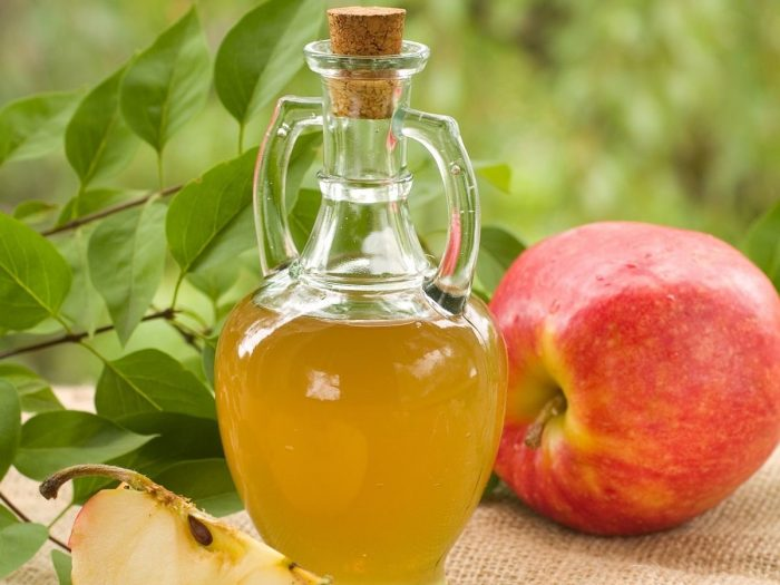 A jar of apple cider vinegar against a green background with whole and halved fresh apples and leaves