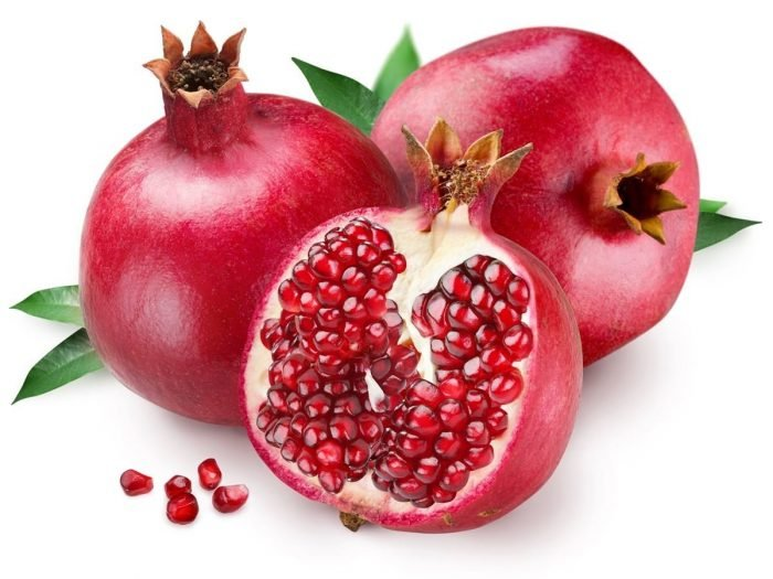 Two fresh pomegranates with a sliced pomegranate on a white background