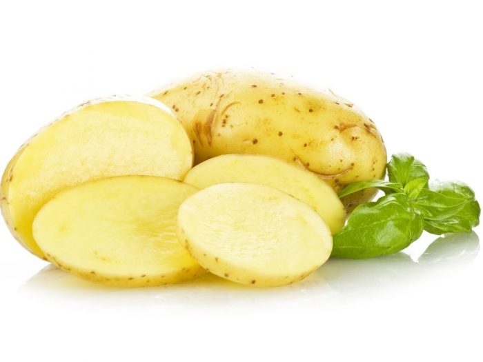 Sliced potato and a whole potato with a leaf beside
