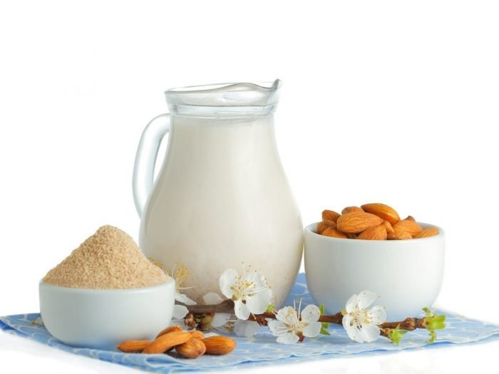 A jug of almond milk, a bowl of almond flour, almond blossoms, and whole nuts