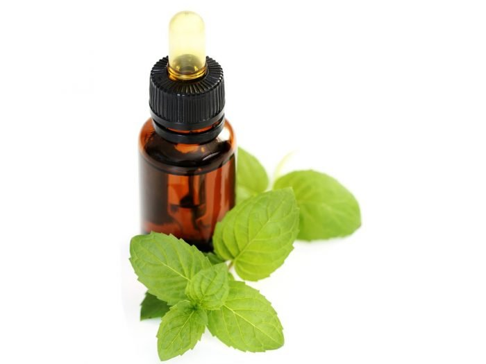 Peppermint oil bottle with fresh peppermint leaves on a white background