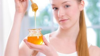 A young beautiful woman holding a small jar of honey