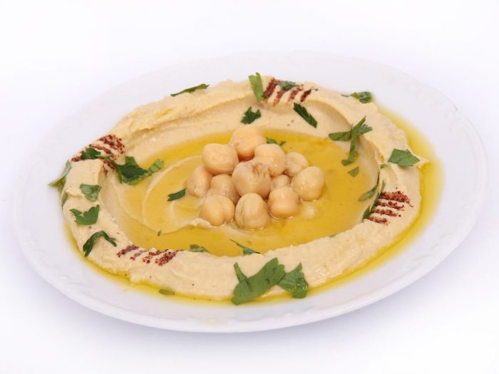 A plate containing hummus garnished with chickpeas and paprika