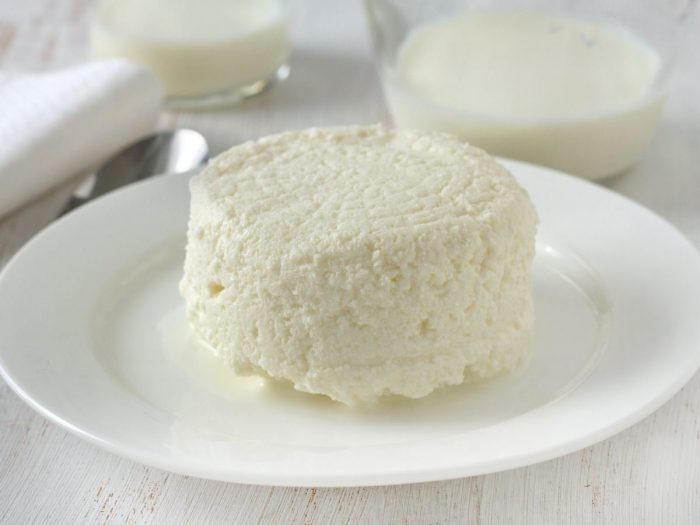A white plate of cottage cheese on a white wooden table