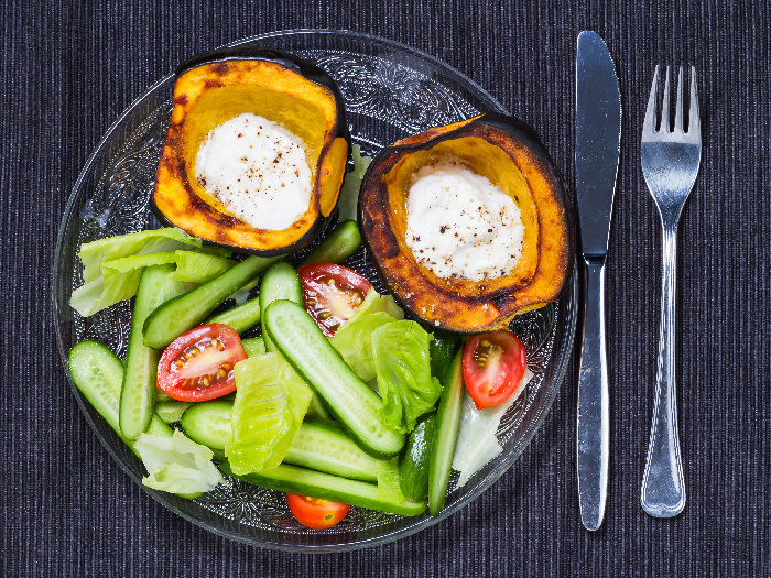Roasted acorn squash with sour cream and salad, served on a glass plate with a fork and knife on the side
