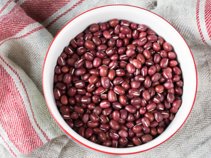 A white bowl of azuki beans on a wooden table