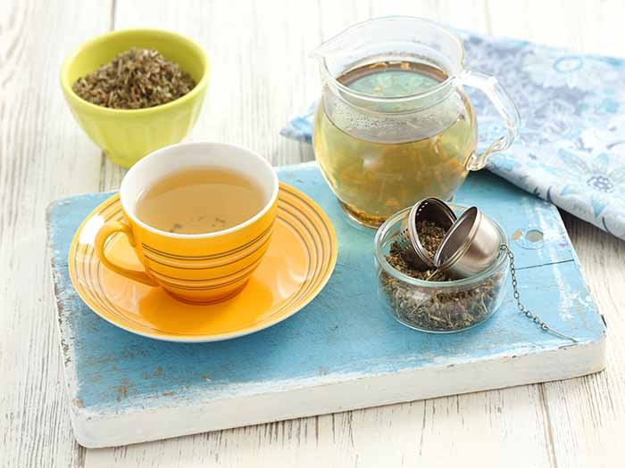 A cup of agrimony tea kept near a bowl of agrimony dried leaves and a pitcher of the tea, on a blue platform