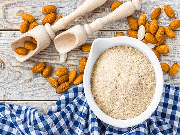 A flat lay picture of a bowl of almond flour kept next to almonds on a wooden table