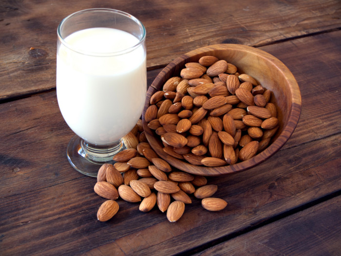 A glass filled with milk and a couple of almonds kept around it