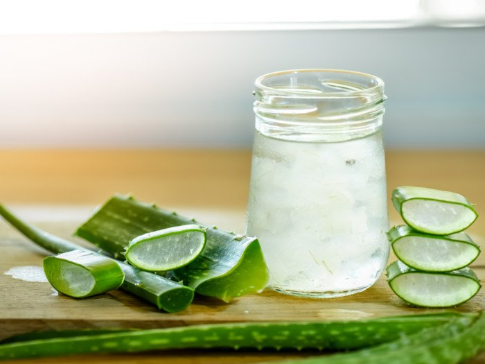 Aloe vera leaf, leaf slices, and aloe juice in a bottle