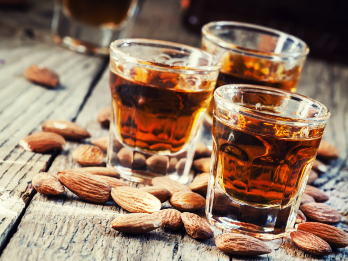 A close-up shot of three glasses of amaretto surrounded by almonds as it is placed on a wooden table