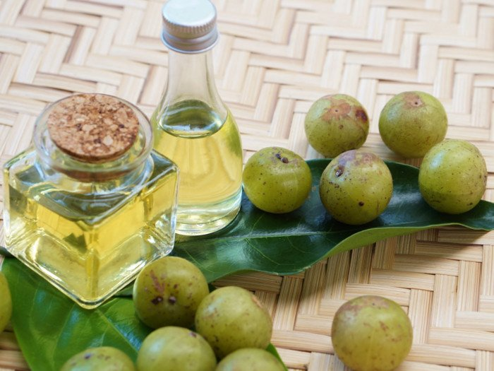 2 bottles of amla oil with fresh amla and leaves on a mat