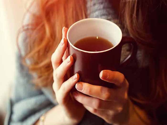 A girl wearing woolen holding a cup of tea in her hands