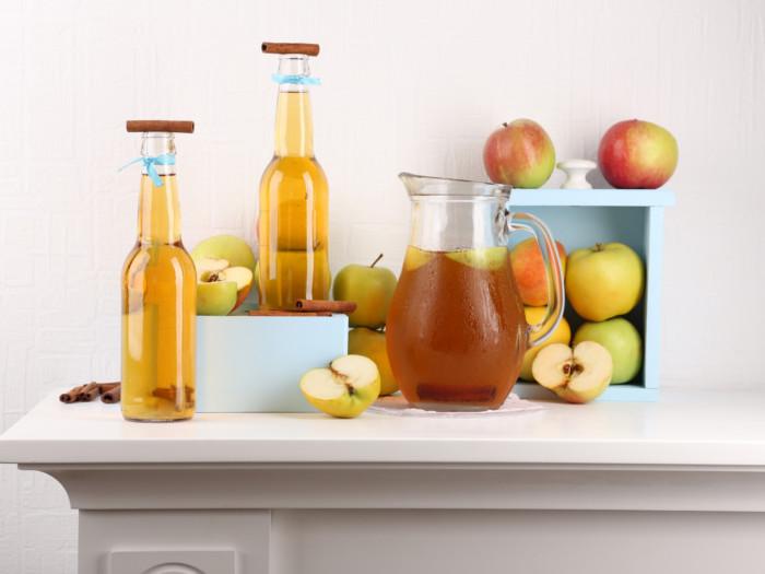 Bottles of apple cider vinegar placed amidst apples against a white background