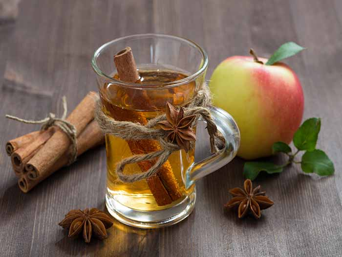 Tea with a cinnamon stick in a glass next to an apple and spices on a wooden table