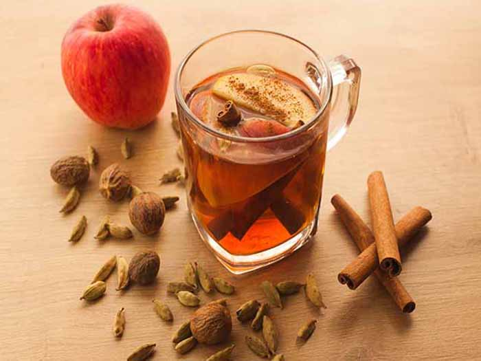A glass of apple cinnamon tea, kept next to an apple and cinnamon sticks
