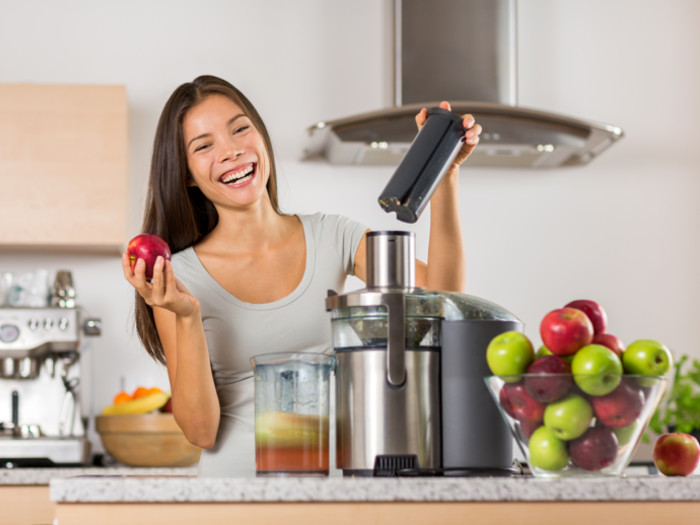 A woman in a modern kitchen making fresh apple juice with a juicer, and green and red apples
