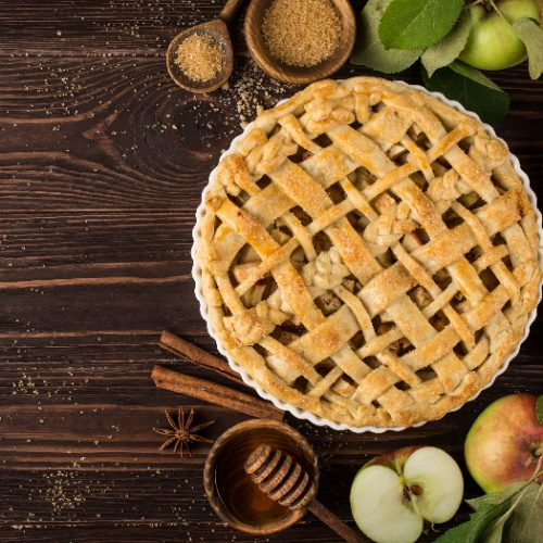 A flat lay picture of an apple pie and ingredients on a wooden background