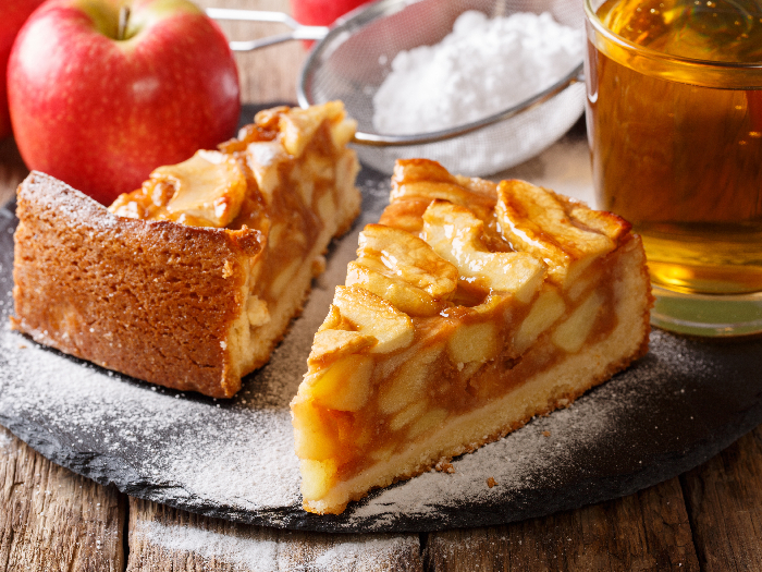 Traditional sliced apple pie close-up on a table and juice kept atop a wooden table