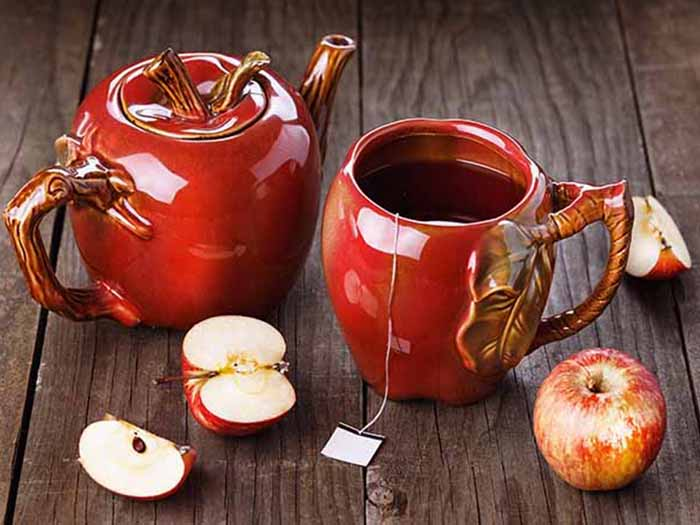 Apple tea in apple-shaped teapot set, with fresh apples on a wooden counter