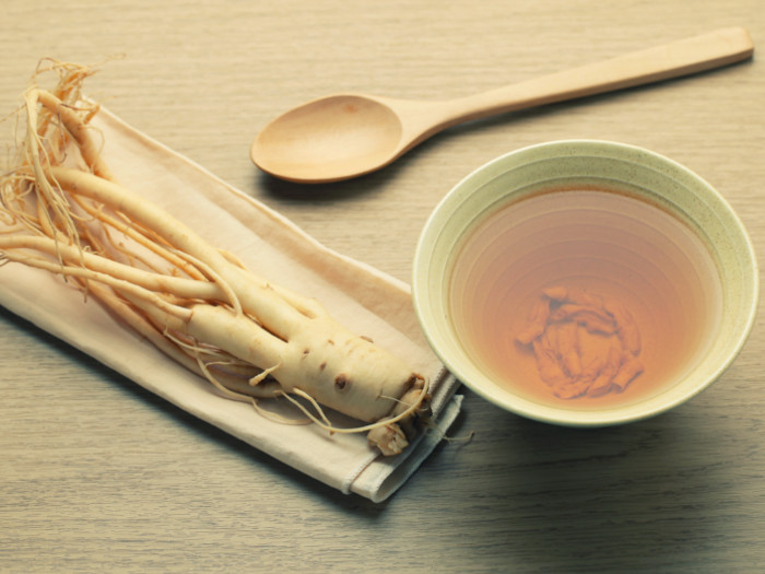 A cup of Ashwagandha tea kept beside a spoon and an ashwagandha root against a brown background