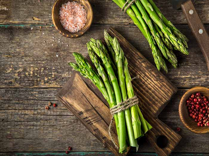 Asparagus stalks tied in bundles on a wooden counter