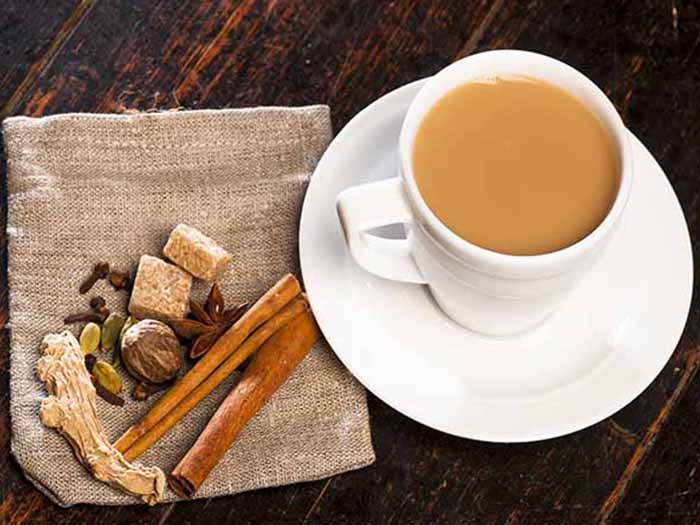 A cup of milky Assam tea, kept atop a wooden table, next to spices kept on a grey colored napkin
