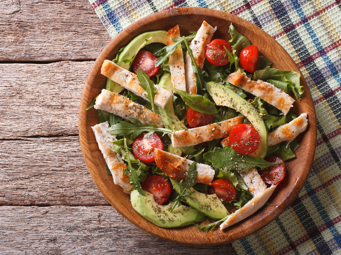 Chicken salad with avocado, arugula and cherry tomatoes in a wooden plate.