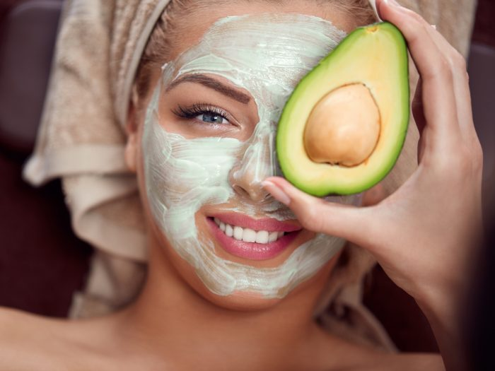 A young woman with an avocado face mask on her face smiling and holding half avocado