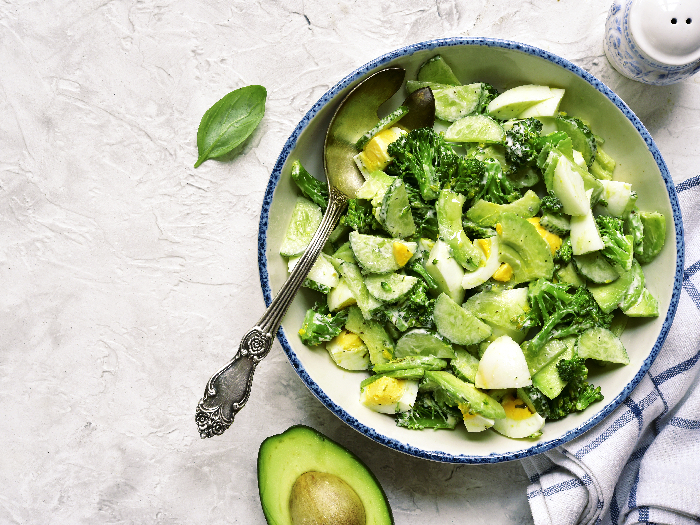 A flat lay picture of avocado salad with broccoli,cucumber and boiled eggs in a white vintage bowl over light slate,stone or concrete background