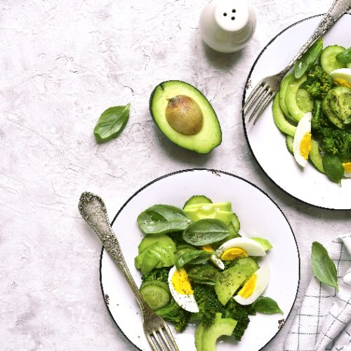 A flat lay picture of two portions of green detox salad with avocado,broccoli,cucumber and eggs on a light slate,stone or concrete background