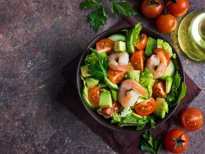 Salad with avocado and shrimps in a bowl