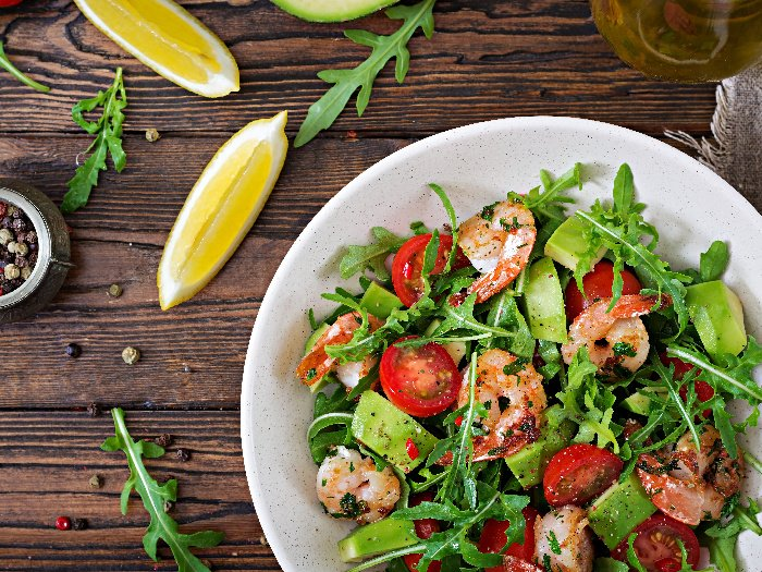 A close-up shot of a salad bowl with shrimp, tomato, avocado and arugula against a wooden background.