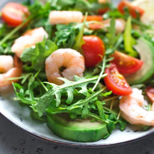 Green salad with Shrimps (prawns), avocado and arugula.