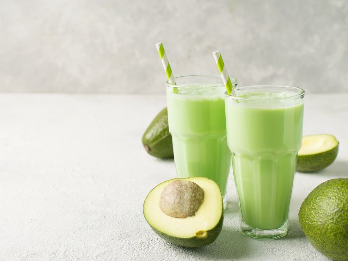 Two glasses of avocado smoothies placed atop a table next to avocados