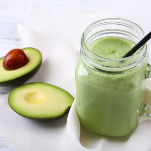 Avocado smoothie in a mason jar with a cut avocado in the background