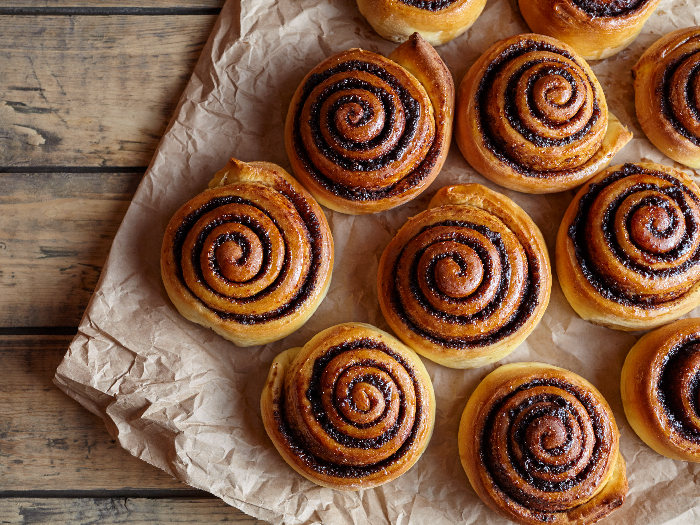 Freshly baked cinnamon buns with spices and cocoa filling on parchment paper