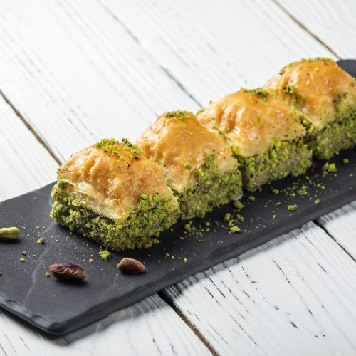 Turkish baklava turkish delight, oriental sweets on a black dish for serving on a wooden white table.