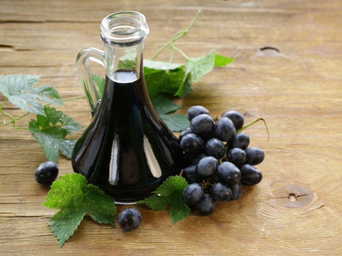 Balsamic vinegar in a bottle with grapes and grape leaves on a wooden surface