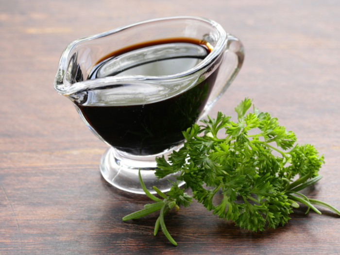 A sauce boat of a dark-colored liquid with a sprig of parsley on a wooden surface.