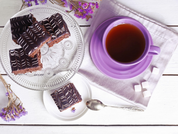 Top view of a teacup with a plate of chocolate biscuits nearby