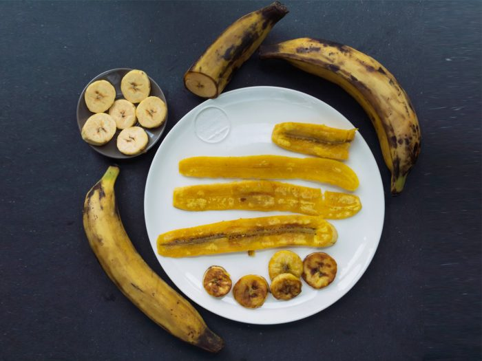 Flatline picture of a plate of plantain chips along with bowl banana slices and bananas on a slate background.