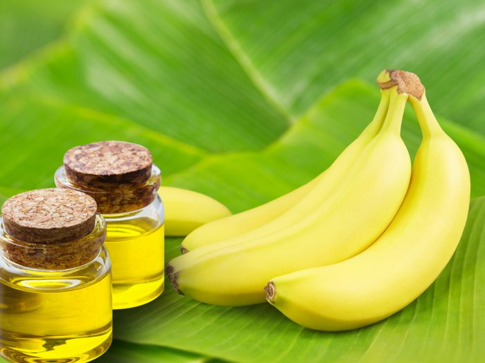 Bananas and banana oil bottles on banana leaves