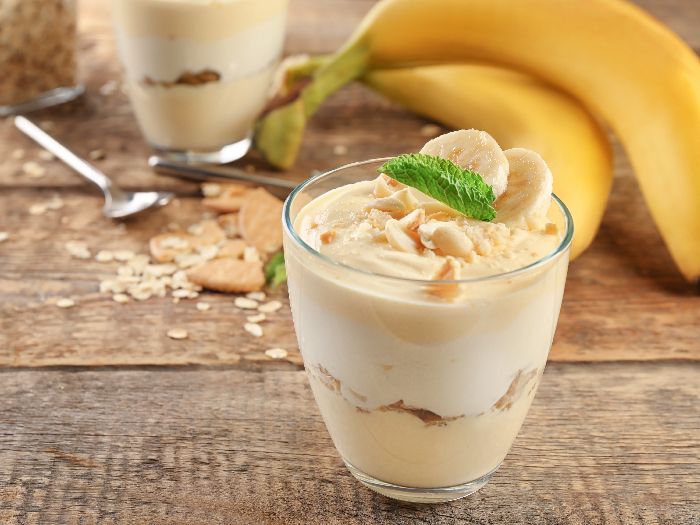 A glass with delicious banana pudding on table