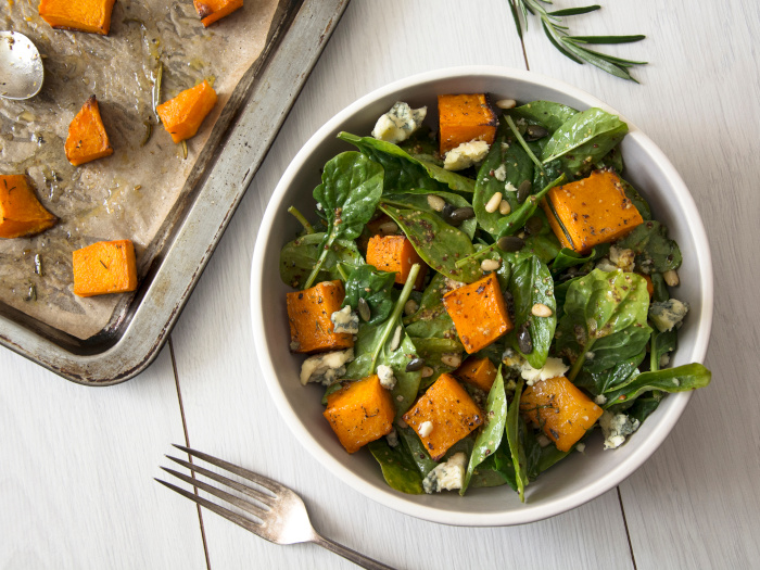 Squash, spinach, and pine nuts salad in a white bowl