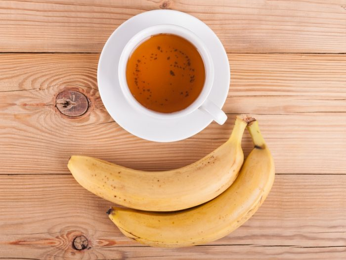 A cup of banana tea with fresh ripe bananas on a wooden table