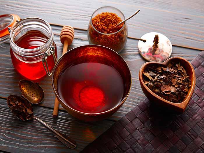Bancha tea kept atop a table, next to dried bancha tea leaves, honey and brown sugar