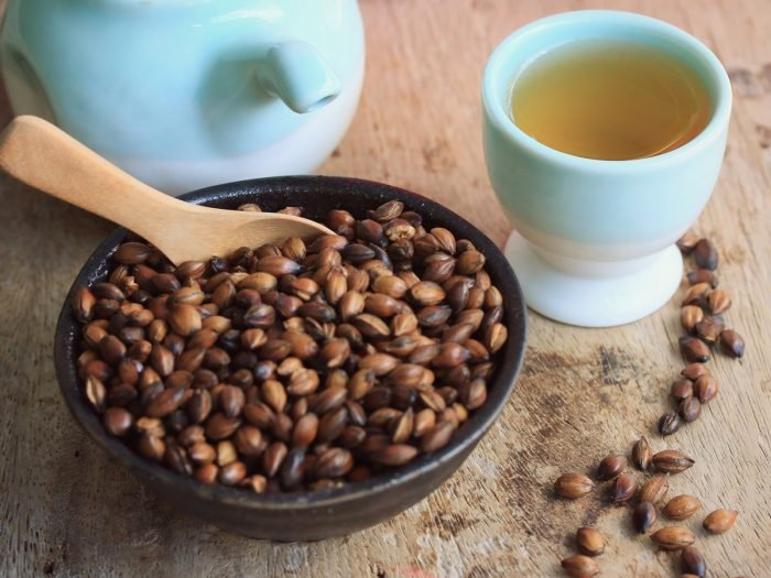 A ceramic bowl of roasted barley seeds with a jar and cup of barley tea on a wooden table