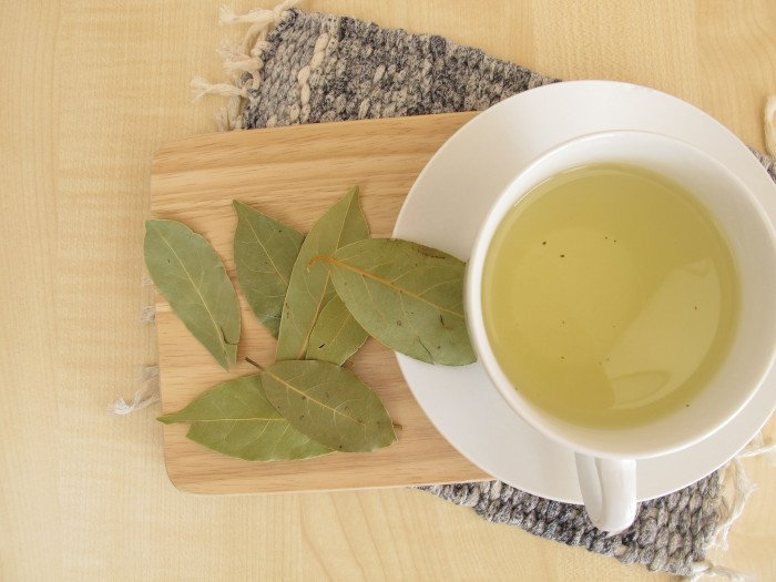A flat lay pic of bay leaf tea in a white cup places on a wooden platform, right next to a bunch of bay leaves